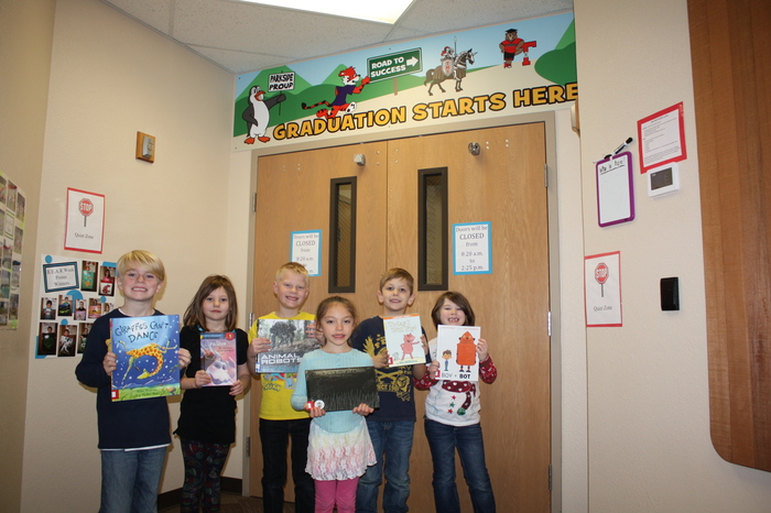 6 students holding new library books from the Tenino Lion's Club.