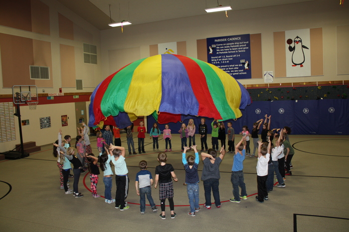 Parkside students using the parachute to learn teamwork.