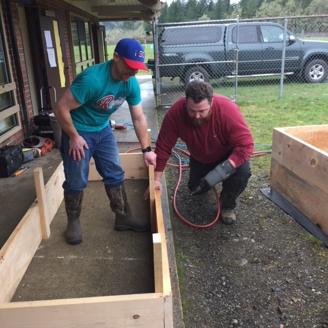 Mr. T and parent volunteer make planter boxes.
