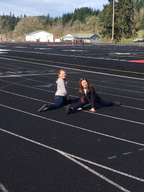 Girls practicing cheer moves on track.